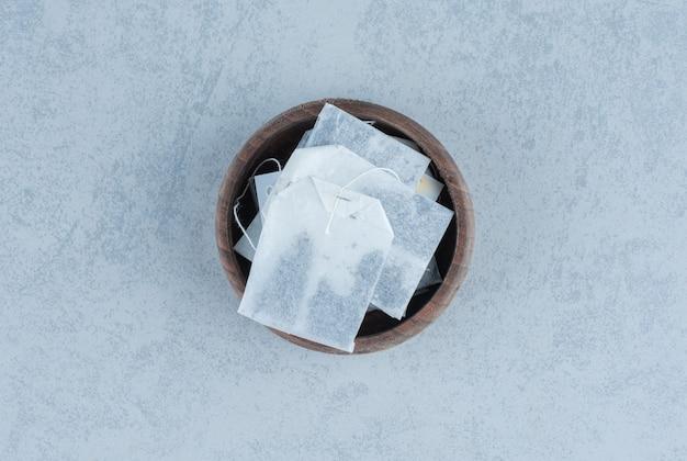 Teebeutel in schüssel auf marmor.