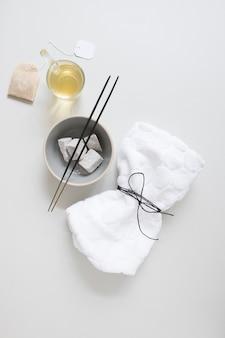 Teebeutel; öl; bimsstein; räucherstäbchen und gebundene serviette auf weiße fläche