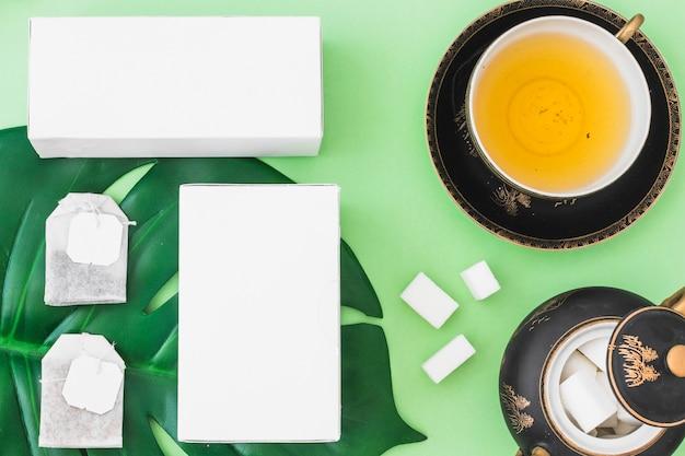 Teebeutel, zuckerwürfel und kästen mit kräuterteeschale auf grünem hintergrund