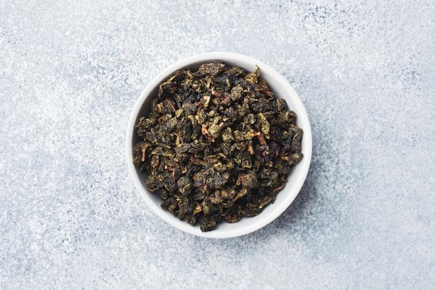 Teeblätter für das brauen in der schüssel auf einem grauen hintergrund.
