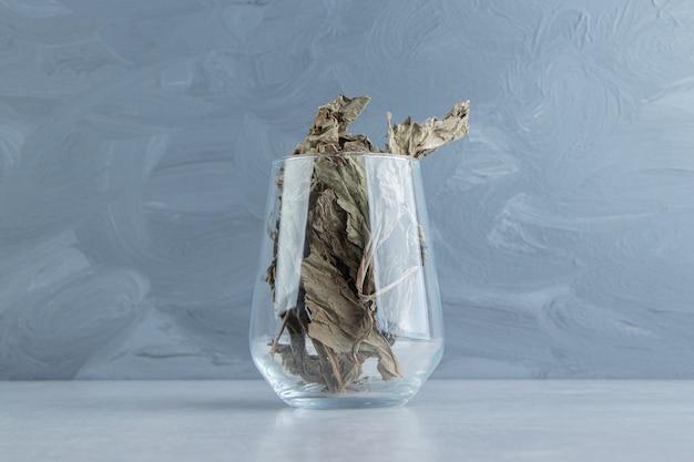 Teeblätter im glas auf steinoberfläche trocknen
