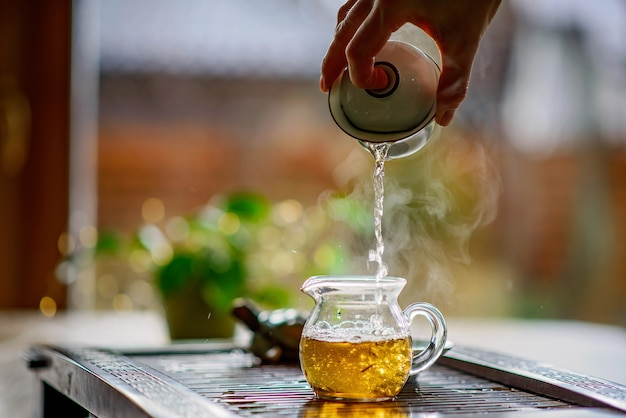 Teebrühprozess, teezeremonie, eine tasse frisch gebrühten grünen oolong-tee, warmes, weiches licht. weicher fokus.