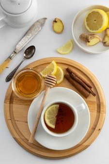 Teecup mit zitrone und honig auf einem weiß. heiße teeschale lokalisiert, draufsichtebenenlage. flach liegen. herbst-, herbst- oder wintergetränk. copyspace.