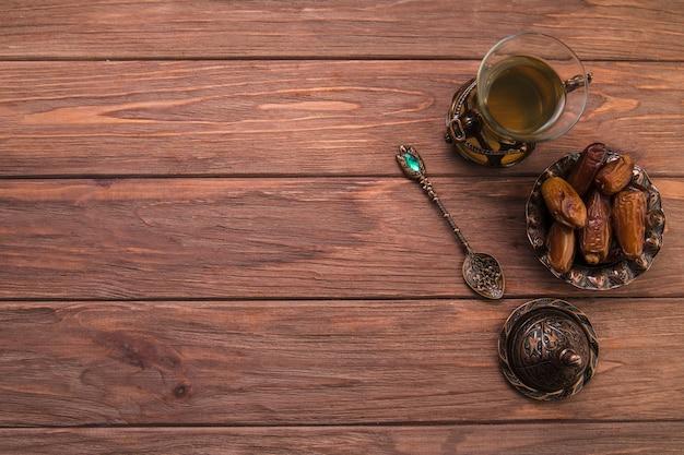 Teeglas mit dattelfrucht in der schüssel