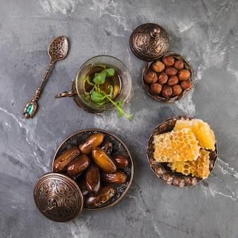 Teeglas mit dattelfrucht und bienenwabe auf tabelle
