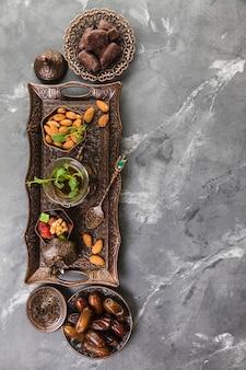 Teeglas mit dattelfrucht und mandeln auf tablett