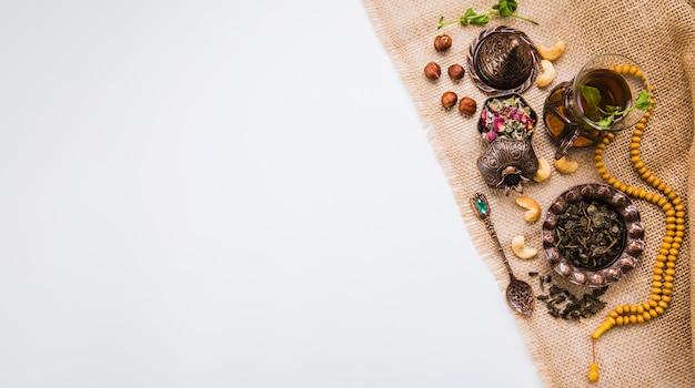Teeglas mit nüssen, kräutern und perlen