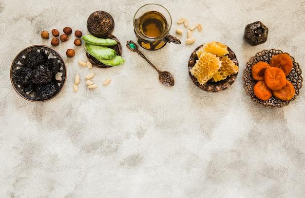 Teeglas mit trockenfrüchten und bienenwabe