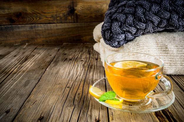 Teeglasschale mit zitrone, minze und gewürzen, auf altem rustikalem holztisch mit warmen decken.