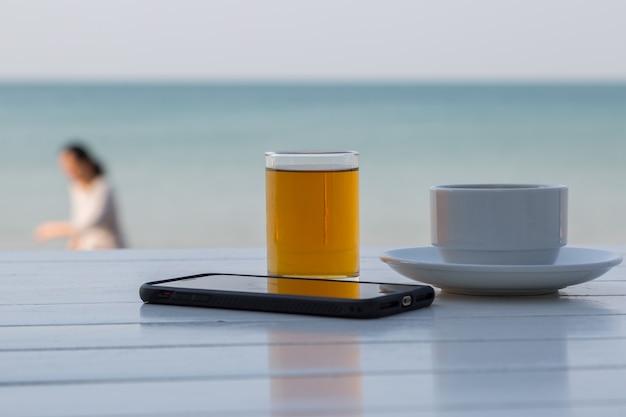 Teekaffee mit intelligentem telefon auf dem weißen holztisch am strandhintergrund