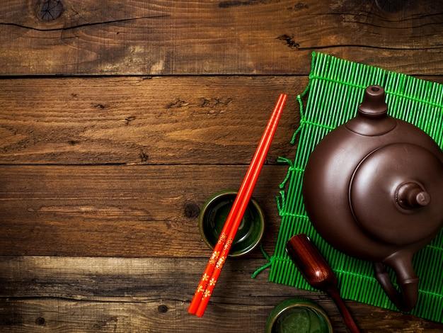 Teekanne auf grüner bambusmatte. ansicht von oben
