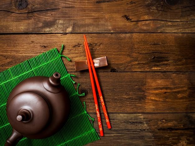 Teekanne auf grüner bambusmatte. draufsicht