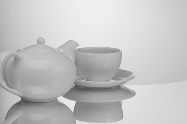 Teekanne aus keramik mit tasse auf hellem hintergrund mit reflexion