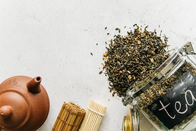 Teekanne aus ton; aufgerolltes tischset mit verschüttetem getrocknetem kräutertee aus dem glas