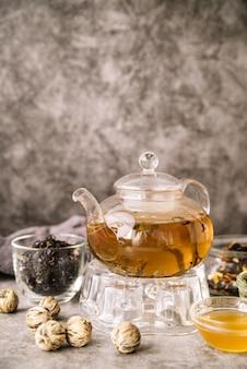 Teekanne gefüllt und walnüsse auf marmorhintergrund