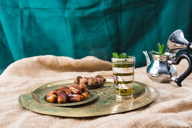 Teekanne in der nähe von tablett mit becher, trockenfrüchten und pralinen auf sackleinen