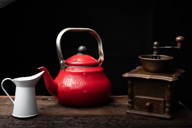 Teekanne kaffeemühle und milchkännchen auf einem dunklen holztisch