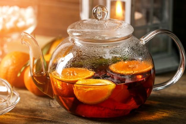Teekanne mandarinentee auf holzuntergrund