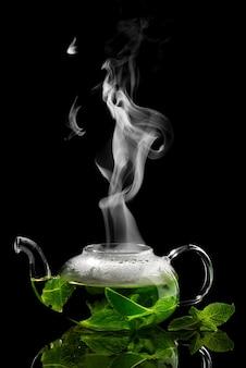 Teekanne mit aufgebrühtem minztee auf schwarzem hintergrund mit aufsteigendem dampf darüber