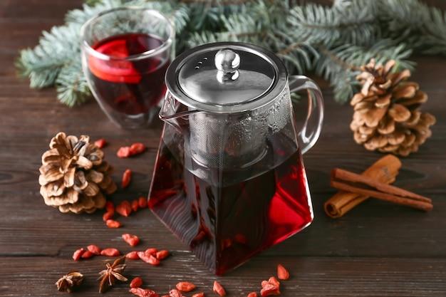 Teekanne mit heißem tee auf holztisch