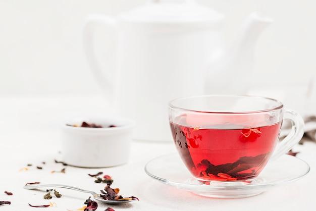 Teekanne mit kräutertee auf dem schreibtisch