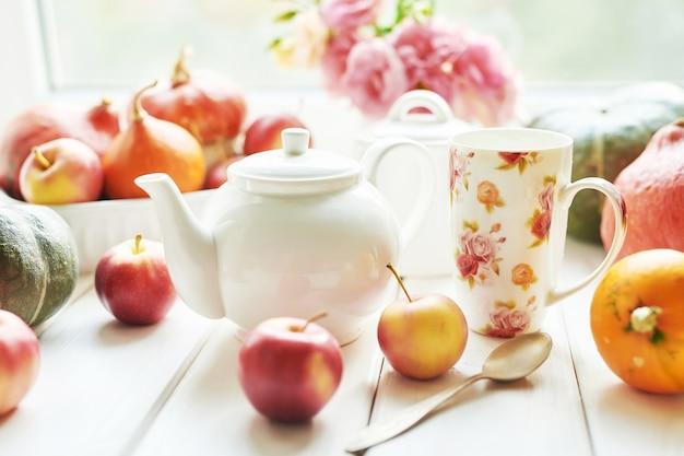 Teekanne mit kürbissen auf thanksgiving-fenster oder halloween-hintergrund