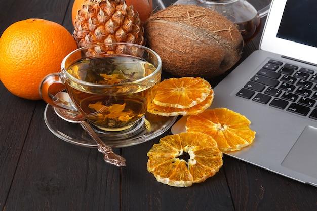 Teekanne mit schwarzem tee, rosen, orangen und grapefruit auf hellem hintergrund
