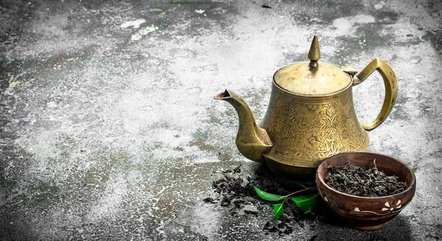 Teekanne mit schwarzem tee.