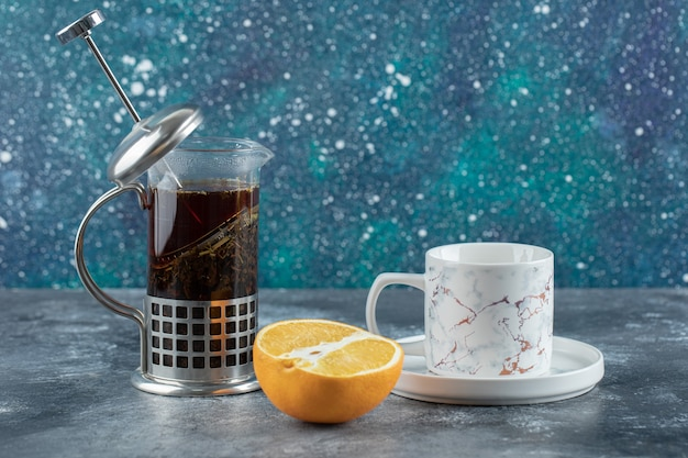 Teekanne mit tasse tee und frischer zitrone über grauem tisch.