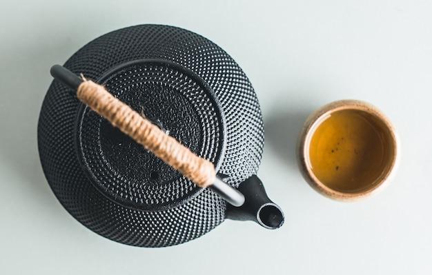 Teekanne mit tee auf hellem hintergrund