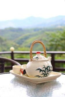 Teekanne mit teetassen mit frischem natürlichem hintergrundkonzept der entspannungs- und pausenzeit