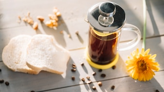 Teekanne mit Toast und Blume auf Holztisch