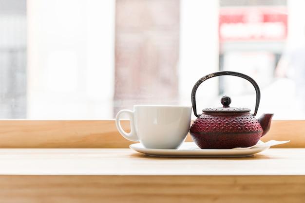 Teekanne mit weißer teeschale auf hölzernem schreibtisch