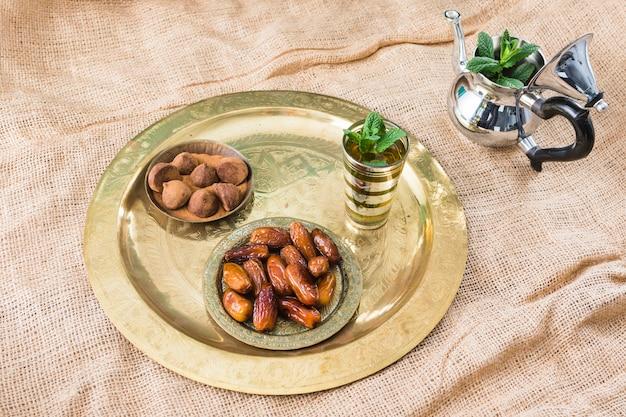 Teekanne nahe becher mit pflanzenzweigen, trockenfrüchten und schokoladenbonbons auf tablett