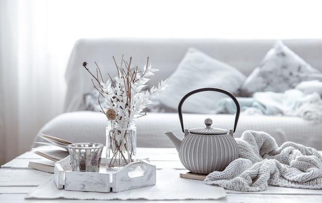 Teekanne und dekor details auf dem tisch im wohnzimmer im hygge-stil. wohnkomfort-konzept.