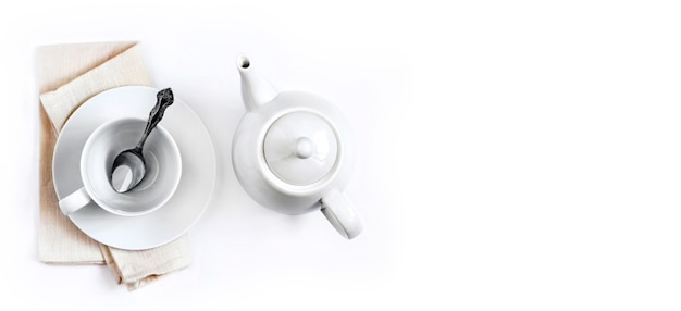 Teekanne und leere teetasse mit löffel auf weißem hintergrund