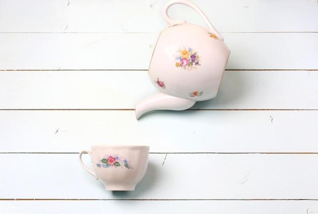 Teekanne und tasse auf einem blauen hölzernen hintergrund