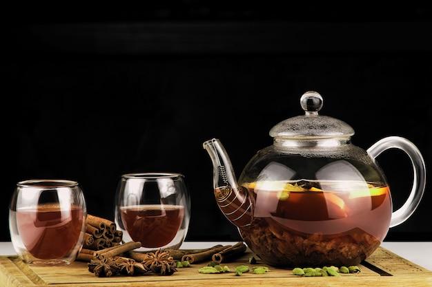 Teekanne und tasse tee auf einem dunklen hintergrund