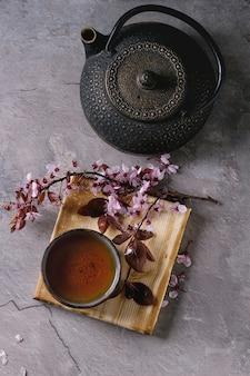 Teekanne und tasse tee mit blütenzweig