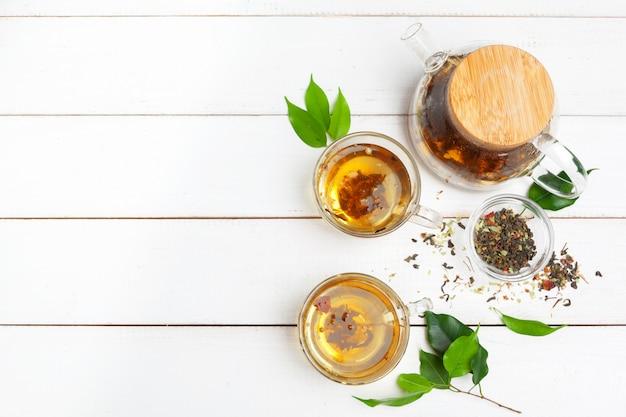 Teekanne und tassen tee auf einem weißen hölzernen hintergrund