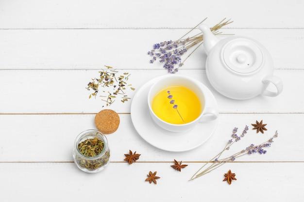 Teekanne und tassen tee auf einem weißen hölzernen