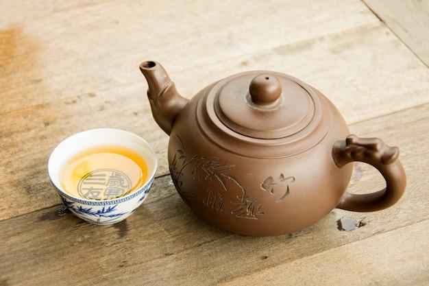 Teekanne und teacups auf hölzernem schreibtisch