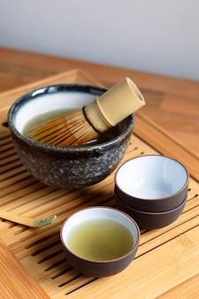 Teekanne und teeservice auf holztablett