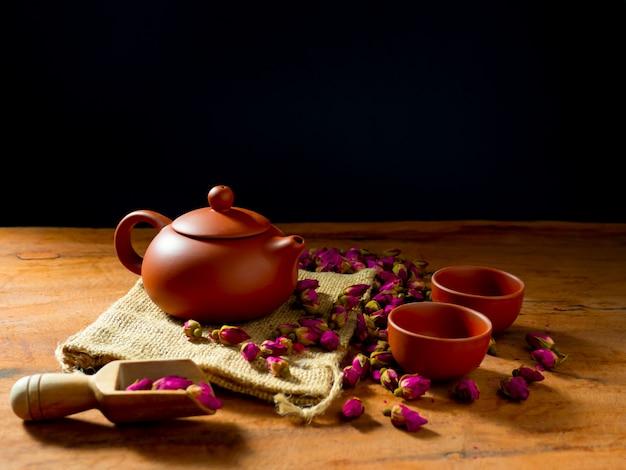 Teekanne und teetasse mit rosenteeblättern auf holztisch und schwarzem hintergrund