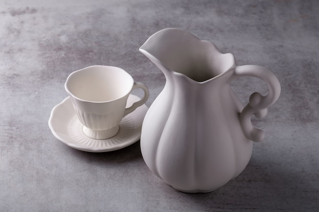Teekannencreme, tasse und untertasse auf zementplatte
