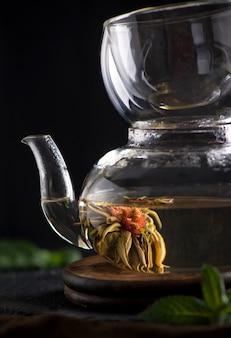 Teekonzept, teekanne mit tee umgeben auf holzhintergrund, teezeremonie, grüner tee in einer transparenten tasse