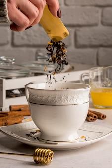 Teekräuter in die tasse gießen