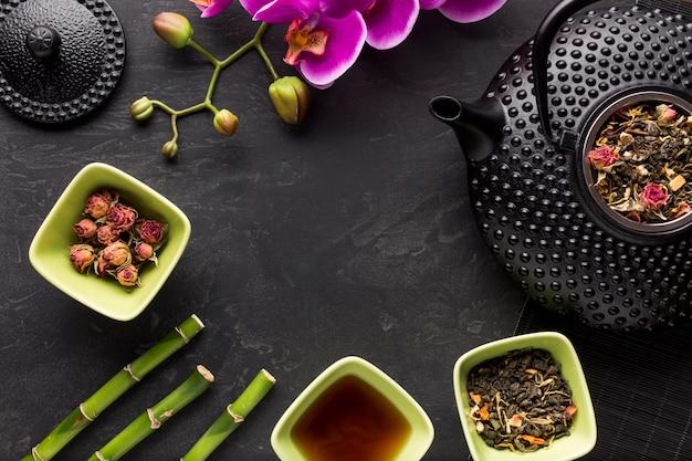 Teekraut mit orchideenblume und -bambus auf schwarzer oberfläche