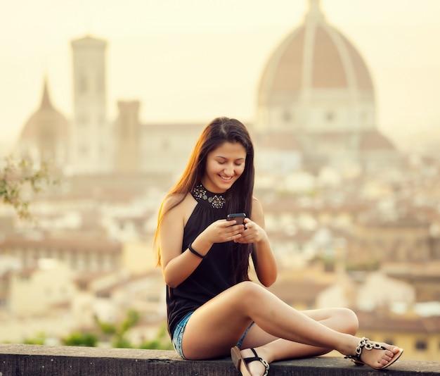 Teen bei sonnenuntergang in florenz nutzt das smartphone