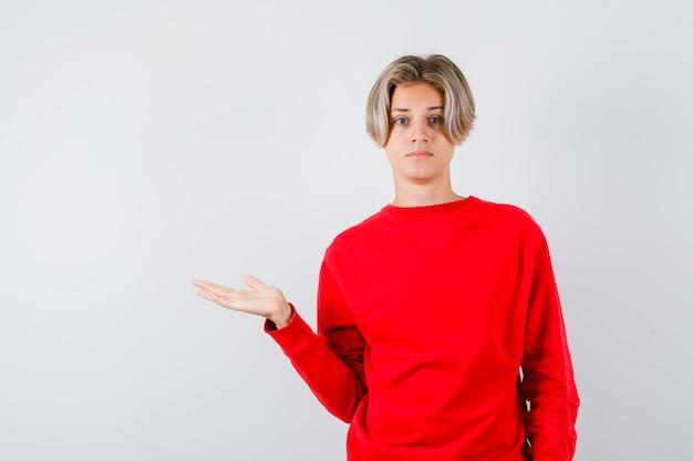 Teen blonde männliche verbreitung palme beiseite im roten pullover und nachdenklich aussehend, vorderansicht.